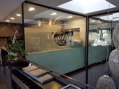 Séparation en verre feuilleté sablé avec logo Brasserie du Corton tenu par pinces acier.