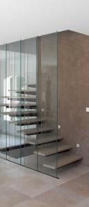 Escalier demi tournant. Structure métallique dans le doublage placo. Marche suspendu rouillé, marche finition béton ciré et garde-corps en verre feuilleté 55/2 tenu en partie haute et basse. Cuges-les-pins