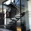 Escalier à limon central en tube acier laminé a chaud avec support de marche en tôle pliées visées. Marches en pierre ep 20mm. Finition en acier brut teinté cirée.. St Tropez