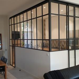 Verrière d'angle séparant un salon du cuisine. Motifs au souhait du client. 2 portes coulissantes donnent accès à cet espace.